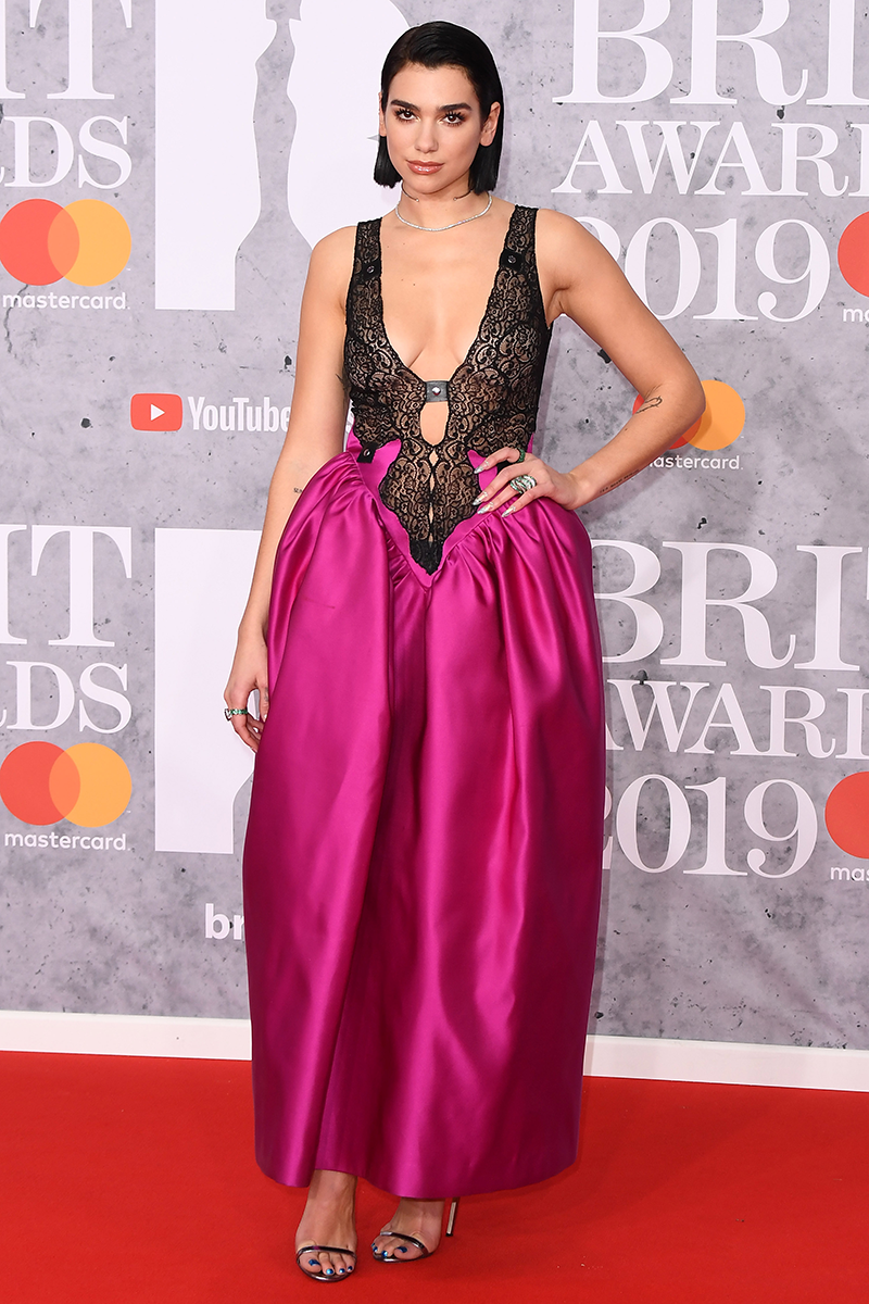 """<p>You really couldn't miss Dua at the <a href=""""https://www.cosmopolitan.com/uk/fashion/celebrity/g26428779/brit-awards-2019-red-carpet-dresses/"""" rel=""""nofollow noopener"""" target=""""_blank"""" data-ylk=""""slk:2019 Brit Awards"""" class=""""link rapid-noclick-resp"""">2019 Brit Awards</a> wearing this sheer lace bodysuit-style top and magenta full skirt situation by Christopher Kane.</p>"""