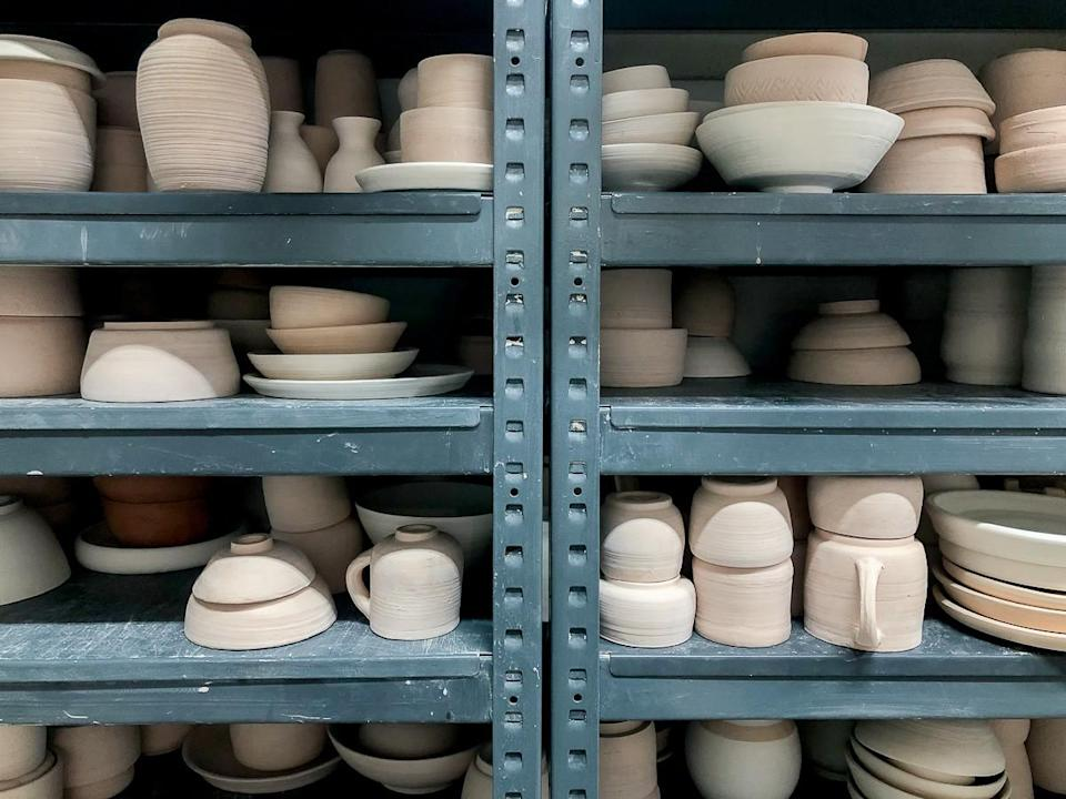 A shelf filled with unfinished pottery products made during the craft workshop