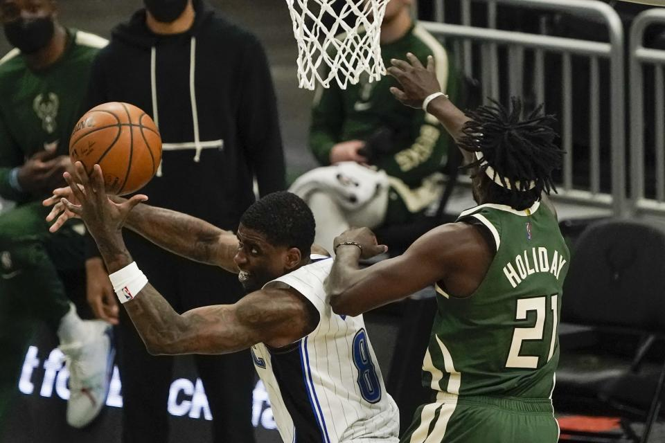 Orlando Magic's Dwayne Bacon tries to shoot past Milwaukee Bucks' Jrue Holiday during the second half of an NBA basketball game Tuesday, May 11, 2021, in Milwaukee. (AP Photo/Morry Gash)