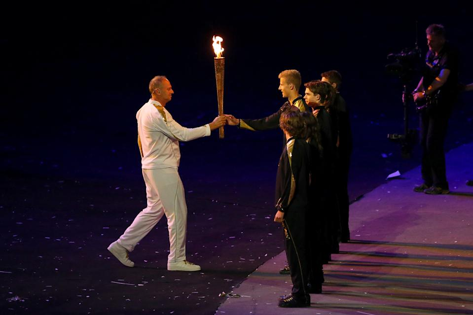 Torchbearer Sir Steve Redgrave receives the Olympic Flame during the Opening Ceremony of the London 2012 Olympic Games at the Olympic Stadium on July 27, 2012 in London, England. (Photo by Alex Livesey/Getty Images)