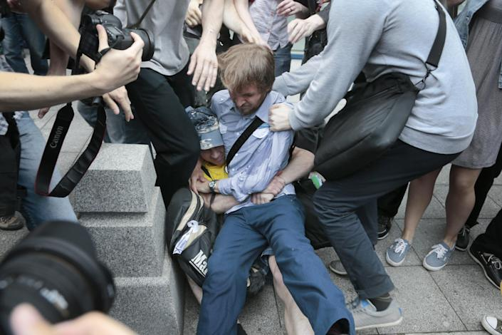 """An anti gay right activist, centre in blue shirt, grapples with a pro gay rights activist outside State Duma, Russia's lower parliament chamber, in Moscow, Russia, Tuesday, June 11, 2013. Protesters attempted to rally outside the Russian State Duma before what is expected to be a final vote on the bill banning """"propaganda of nontraditional sexual relations."""" More than two dozen activists were detained in Moscow on Tuesday as they were protesting a bill that stigmatizes the gay community and bans the giving of information about homosexuality to children. (AP Photo/Ivan Sekretarev)"""