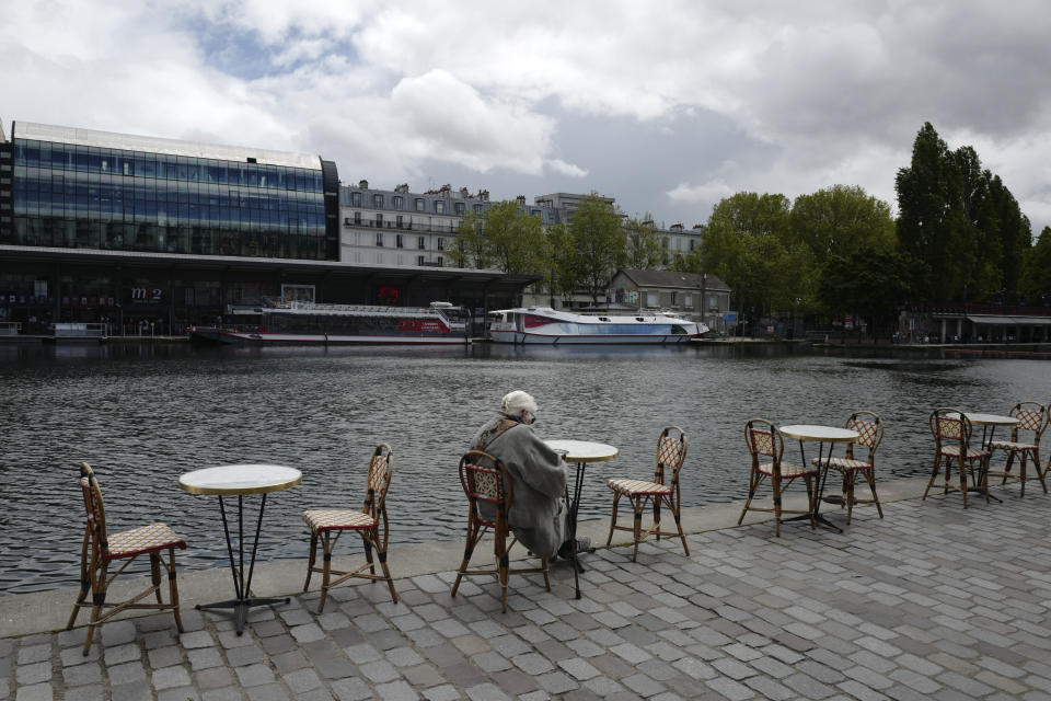 A woman sit at a cafe terrace along the Seine river Wednesday, May, 19, 2021 in Paris. Cafe and restaurant terraces reopened Wednesday after a six-month coronavirus shutdown deprived residents of the essence of French life — sipping coffee and wine with friends. (AP Photo/Rafael Yaghobzadeh)