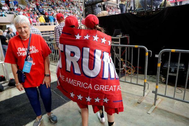 PHOTO: Lori Broughton, right, and Lydia Roy, both of Lafayette, La., walk through the arena wrapped in a Trump campaign flag, before President Donald Trump arrives to speak at a campaign rally in Lake Charles, La., Oct. 11, 2019. (Gerald Herbert/AP)