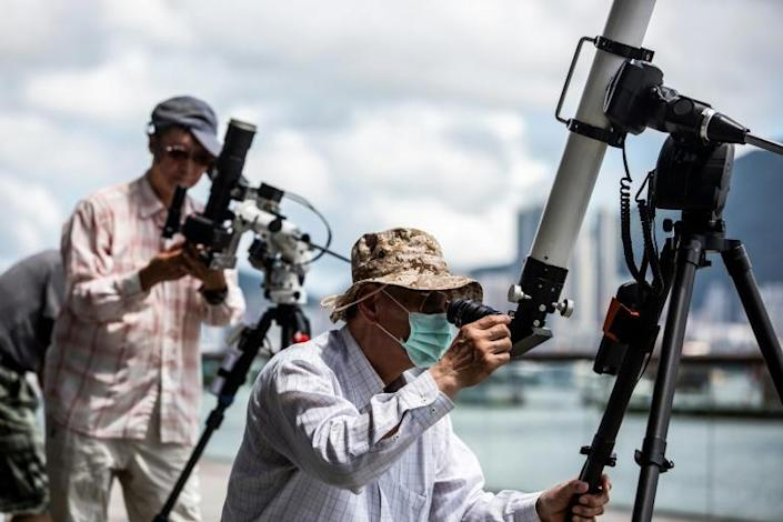 Skywatchers gathered on a Hong Kong waterfront to observe the spectacle (AFP Photo/ISAAC LAWRENCE)