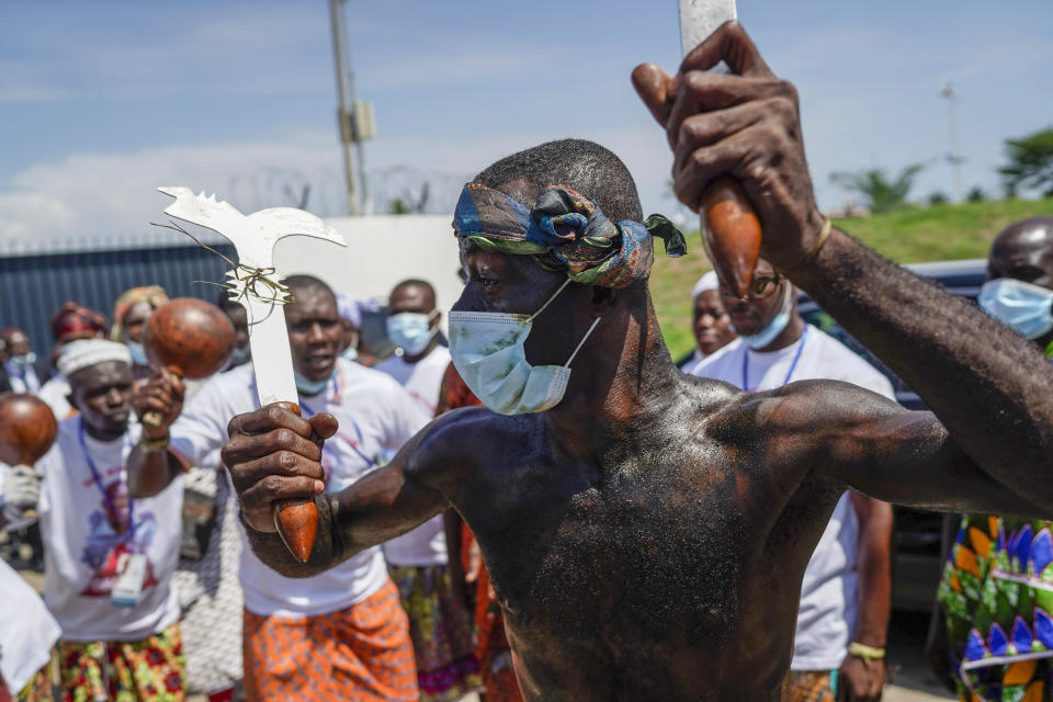 Supporters of the former Ivorian president Laurent Gbagbo take part in a traditional dance as they celebrate before his arrival in Abidjan, Ivory Coast, Thursday, June 17, 2021. After nearly a decade, Gbagbo returns to his country after his acquittal on war crimes charges was upheld at the International Criminal Court earlier this year. (AP Photo/Leo Correa)