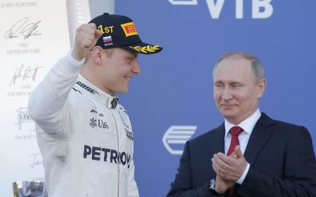 Formula One - F1 - Russian Grand Prix - Sochi, Russia - 30/04/17 - Mercedes Formula One driver Valtteri Bottas of Finland celebrates the victory on the podium, with Russian President Vladimir Putin seen in the background. REUTERS/Maxim Shemetov