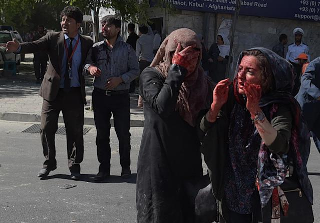 <p>Wounded Afghan women and men gesture at the site of a car bomb attack in Kabul on May 31, 2017.<br> At least 40 people were killed or wounded on May 31 as a massive blast ripped through Kabul's diplomatic quarter, shattering the morning rush hour and bringing carnage to the streets of the Afghan capital. (Photo: Shah Marai/ AFP/Getty Images) </p>