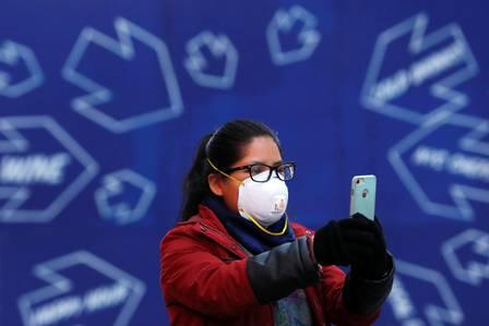 87563483_A woman in a face mask takes a photo in Times Square as the coronavirus disease COVID-19 co.jpg