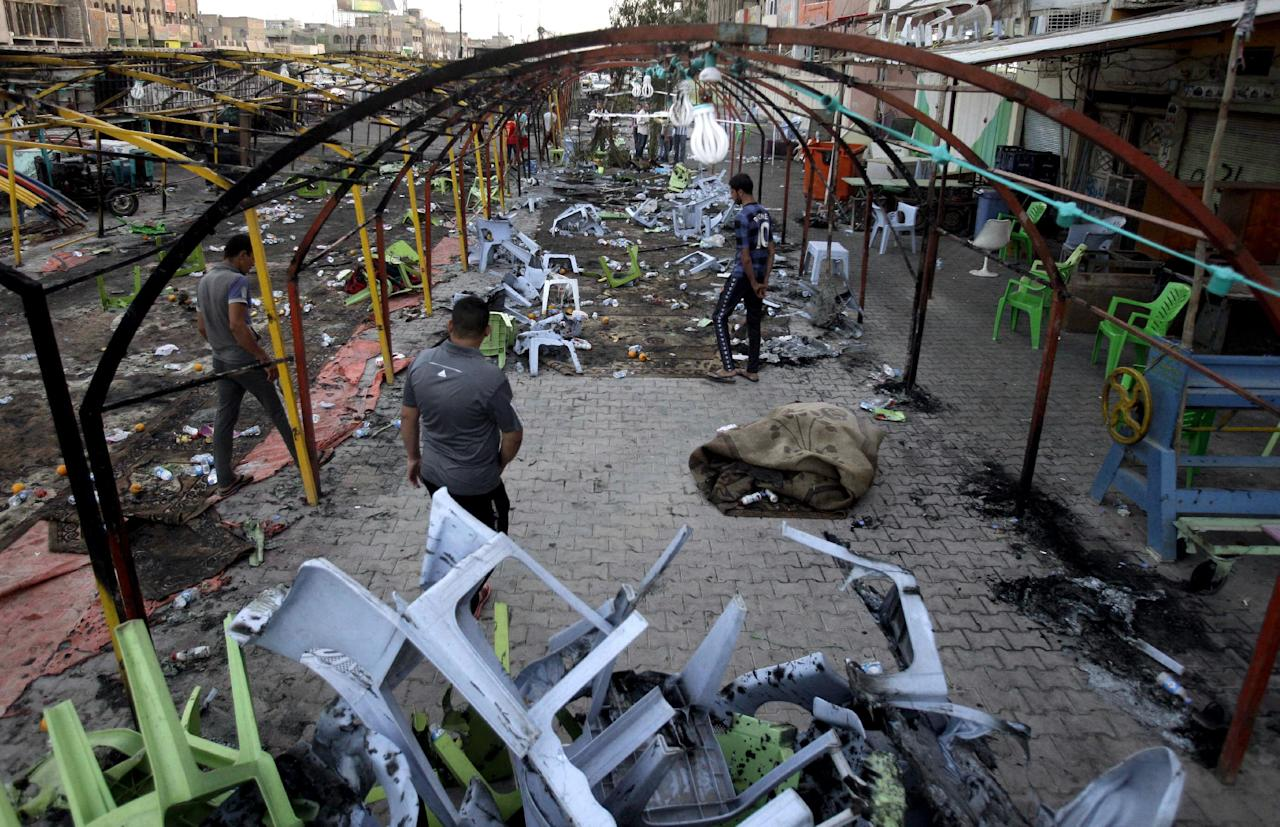 Sunday, Sept. 22, 2013: Baghdad_ People inspect the site of a double suicide bomb attack in the Shiite neighborhood of Sadr City. Two suicide bombers, one in an explosives-laden car and the other on foot, hit a cluster of funeral tents packed with mourning families, killing scores of people during the deadliest of a string of attacks around Iraq. (AP Photo/Karim Kadim)