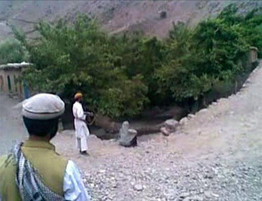 A frame grab shows a man pointing an AK47 rifle at a 22 year old woman named as Najiba (C), who is sitting on the edge of a ditch shortly before being executed by gunfire in Qol village, Parwan province, north of Kabul. Najiba was married to a member of a hardline Taliban militant group and was accused of adultery with a Taliban commander