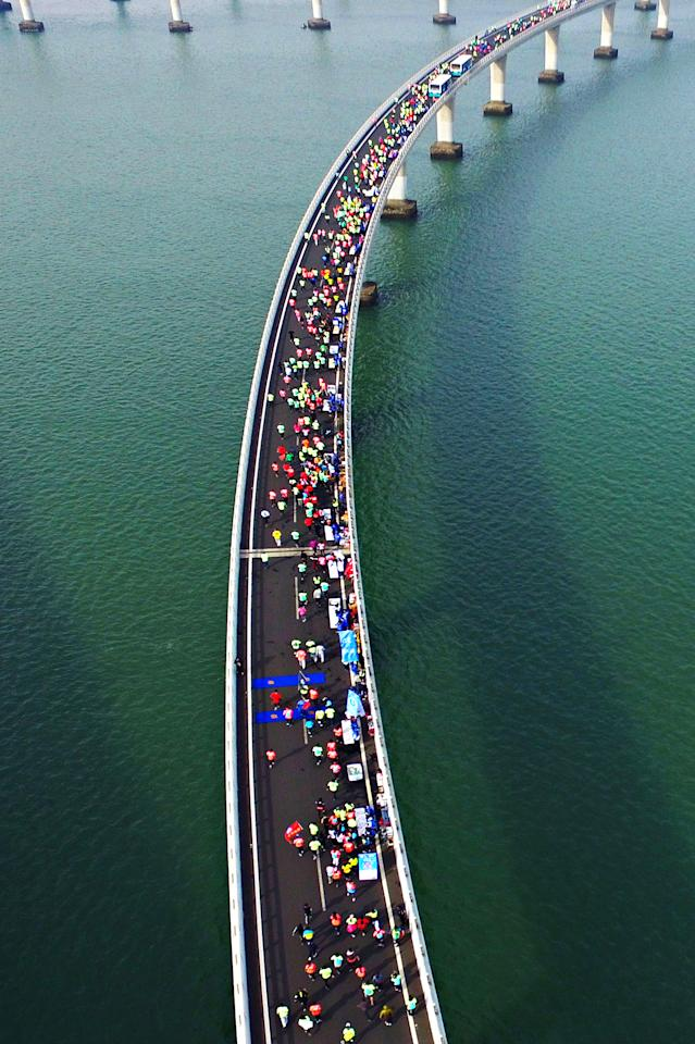 <p>This photo taken on November 19, 2017 shows participants crossing the Jiaozhou Bay Bridge as they compete in the 2017 Qingdao International Marathon on the Sea in Qingdao in China's eastern Shandong province. (STR/AFP/Getty Images) </p>