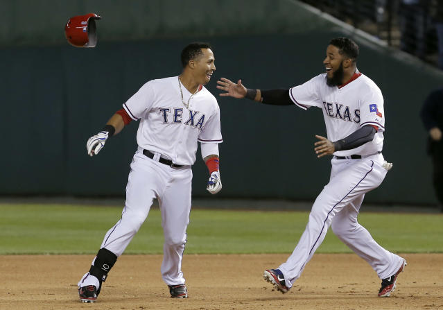 Texas Rangers Leonys Martin, left, is congratulated by teammate Elvis Andrus after hitting an RBI-single to win in the ninth inning of a baseball game against the Seattle Mariners, Wednesday, April 16, 2014, in Arlington, Texas. Texas won 3-2. (AP Photo/Brandon Wade)