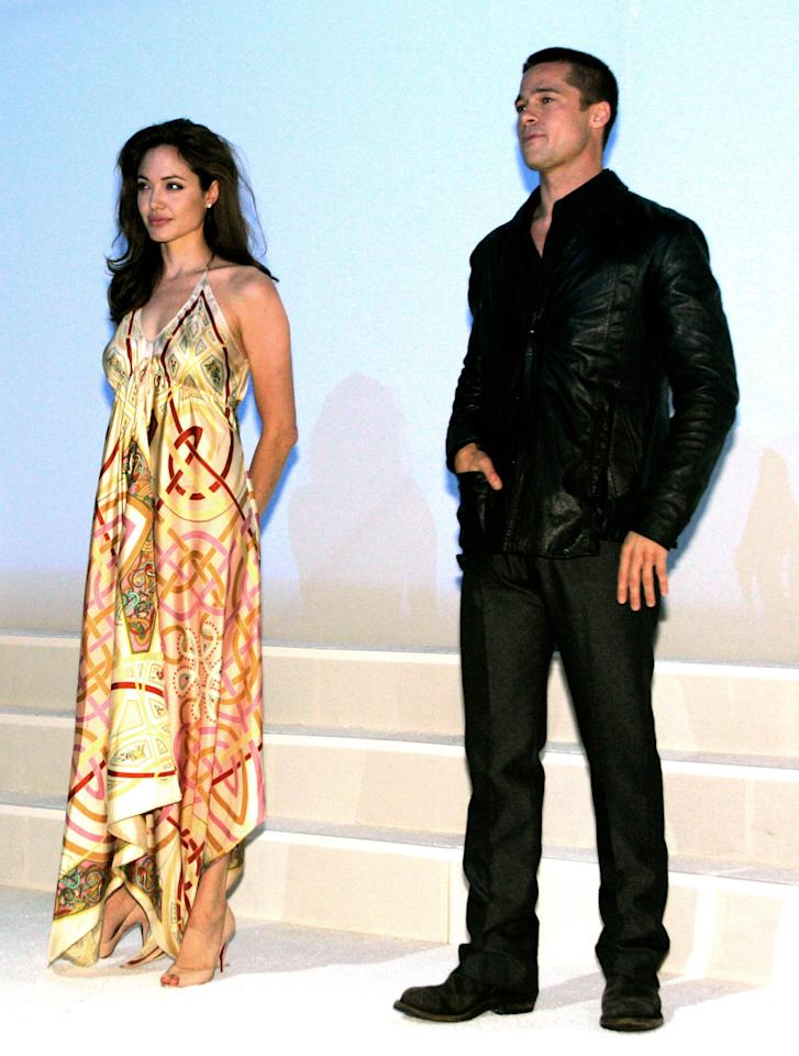"File photo of actress Angelina Jolie and actor Brad Pitt onstage at the 20th Century Fox ShoWest presentation in Las Vegas, Nevada March 17, 2005. Jolie poured cold water on the rumors of a romance with leading man Brad Pitt, telling Marie Claire magazine in an upcoming issue that the two are not intimate. For months, speculation has swirled around the world that Pitt, 41, and Jolie, 30, were having a romantic affair since filming ""Mr. & Mrs. Smith"" last year. Picture taken March 17, 2005. REUTERS/Ethan Miller/FILE   EM/GN"