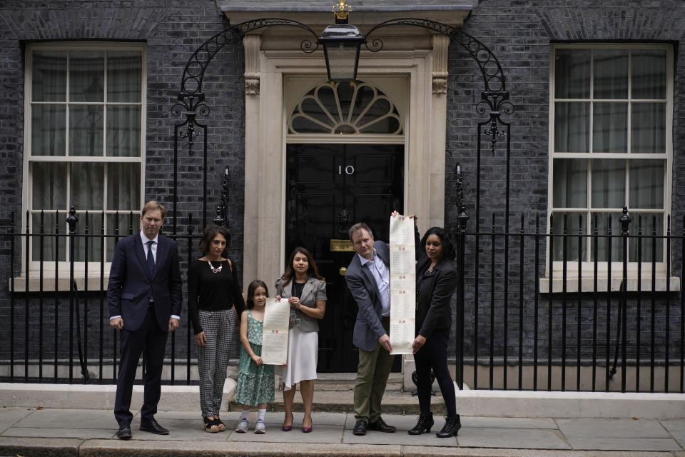 Imprisoned British-Iranian woman Nazanin Zaghari-Ratcliffe's husband Richard Ratcliffe, second right, and their seven year old daughter Gabriella pose for the media with, from left, Conservative Party MP Tobias Ellwood, Elika Ashoori whose British-Iranian father Anoosheh Ashoori is detained in Iran, and Labour Party MPs Tulip Siddiq and Janet Daby holding a petition outside 10 Downing Street, London, on the day marking 2,000 days since Nazanin Zaghari-Ratcliffe has been detained in Iran, Thursday, Sept. 23, 2021. Zaghari-Ratcliffe was originally sentenced to five years in prison after being convicted of plotting the overthrow of Iran's government, a charge that she, her supporters and rights groups deny. While employed at the Thomson Reuters Foundation, the charitable arm of the news agency, she was taken into custody at the Tehran airport in April 2016 as she was returning home to Britain after visiting family. (AP Photo/Matt Dunham)