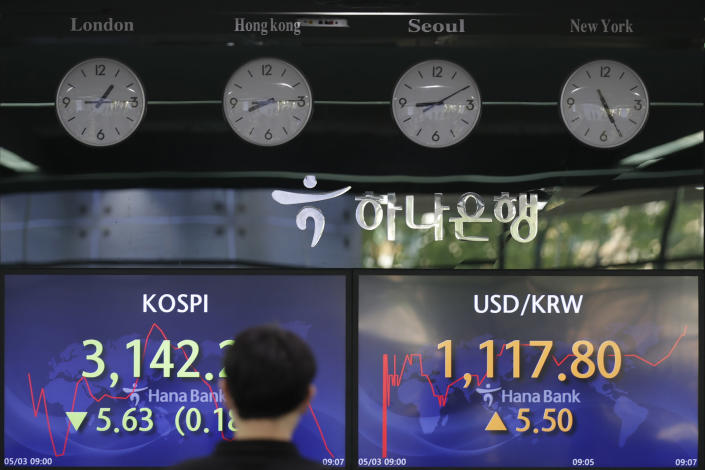 A currency trader walks near screens showing the Korea Composite Stock Price Index (KOSPI), left, and the foreign exchange rate between U.S. dollar and South Korean won at a bank's foreign exchange dealing room in Seoul, South Korea, Monday, May 3, 2021. Shares were mostly lower in Asia in thin trading Monday, with many markets including those in Tokyo and Shanghai closed for holidays. (AP Photo/Lee Jin-man)