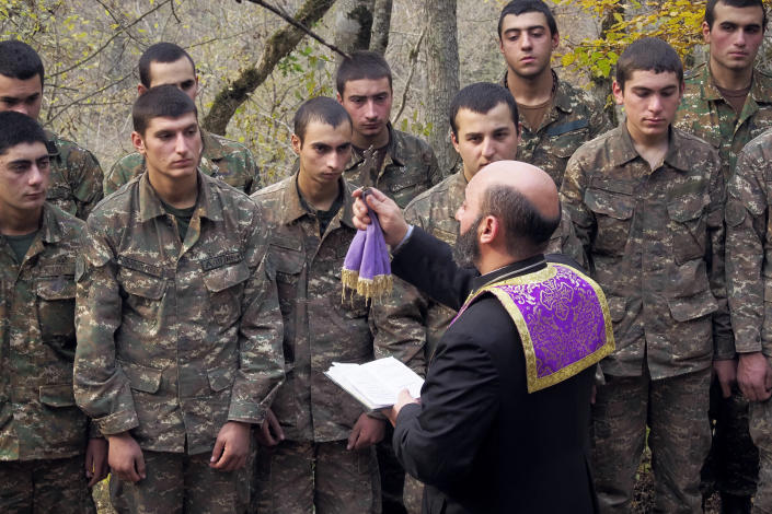 Priest Aristakes Hovhannisyan conducts a baptism ceremony for ethnic Armenian soldiers in a military camp near the front line during a military conflict in separatist region of Nagorno-Karabakh, Monday, Nov. 2, 2020. Fighting over the separatist territory of Nagorno-Karabakh entered sixth week on Sunday, with Armenian and Azerbaijani forces blaming each other for new attacks. (AP Photo)