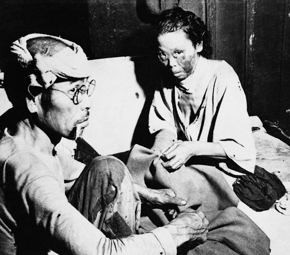 A Japanese man and woman, victims of the atomic bombing of Hiroshima, sit in a damaged bank building converted into a hospital near the centre of the town in Japan on Oct. 6, 1945. The woman's face is severely scarred by the tremendous heat generated by the explosion. The burns show a pronounced reddish cast.