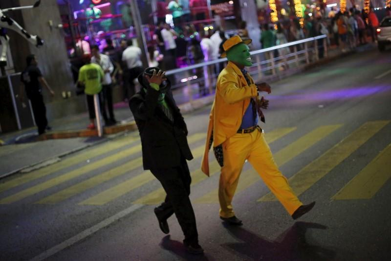 <p>Men dressed as 'The Mask' walk on a street in Cancun, October 12, 2015. <i>(Photo: Reuters/Edgard Garrido)</i></p>