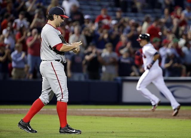 Washington Nationals starting pitcher Tanner Roark, left, wipes the ball as Atlanta Braves' Ramiro Pena, right, rounds the bases after hitting a three-run home run in the second inning of a baseball game, Friday, April 11, 2014, in Atlanta. (AP Photo/David Goldman)