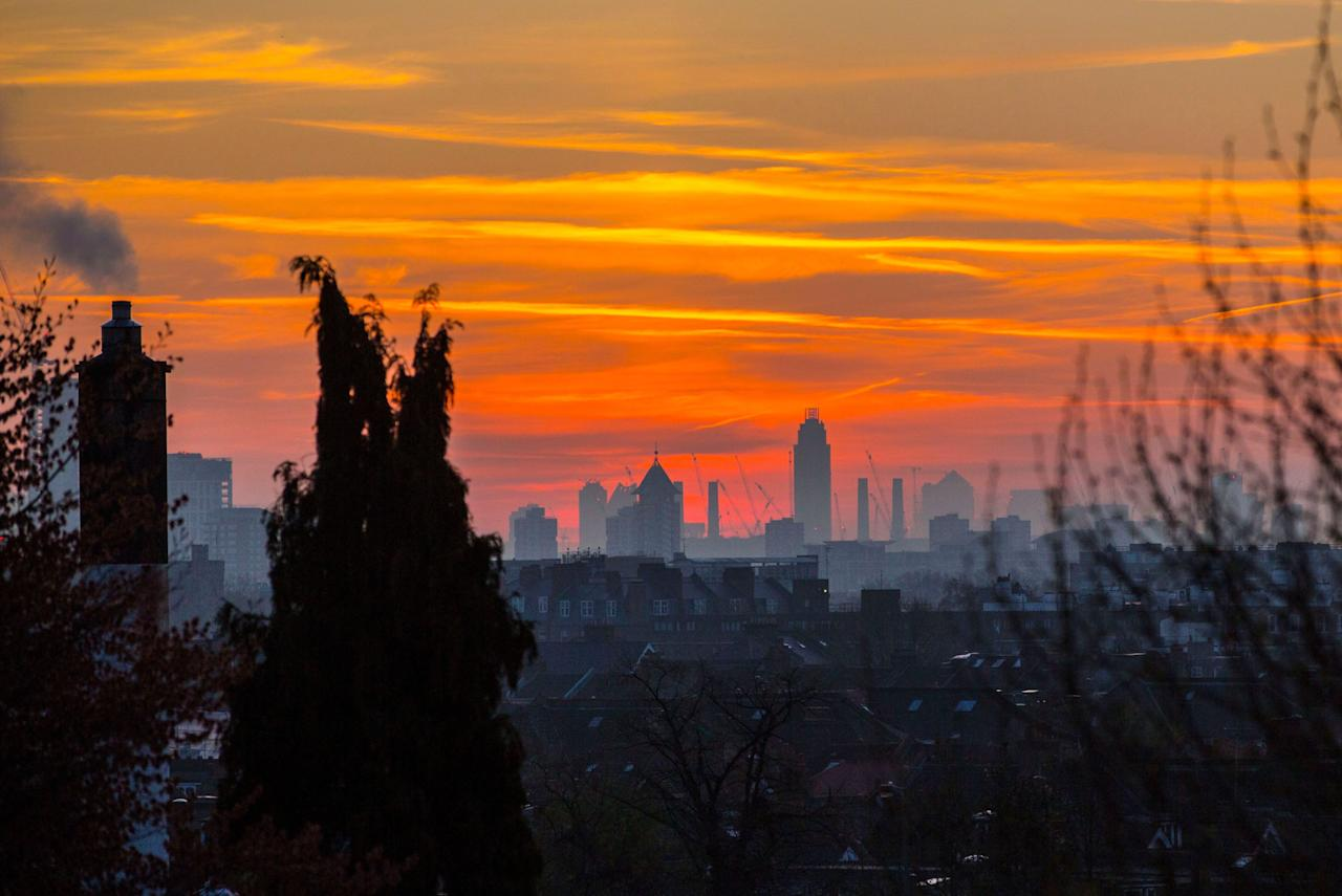 <p>A colourful sky looms behind the London skyline this morning before the sun rises on what will be yet another warm day. Londoners will be enjoying the weather again today as high temperatures are set to continue in the capital. (Rex) </p>