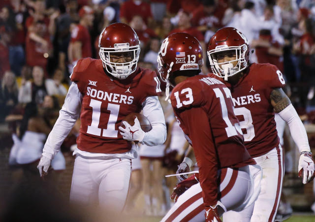 Oklahoma cornerback Parnell Motley (11) celebrates with teammates Tre Norwood (13) and Kahlil Haughton (8) after intercepting a pass in overtime to end an NCAA college football game against Army in Norman, Okla., Saturday, Sept. 22, 2018. Oklahoma won 28-21 in overtime. (AP Photo/Sue Ogrocki)