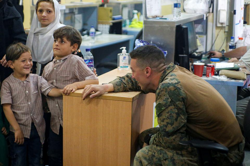 A U.S. Marine assigned to 24th Marine Expeditionary Unit interacts with children during an evacuation at Hamid Karzai International Airport, Afghanistan, August 18, 2021. (U.S. Marine Corps/Lance Cpl. Nicholas Guevara/Handout via Reuters)