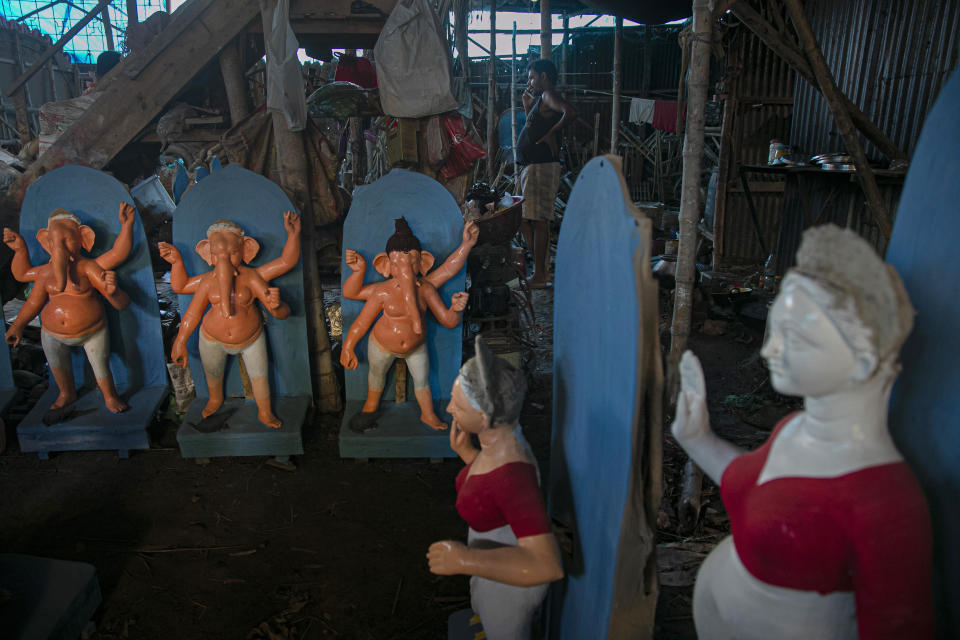 An Indian artisan speaks on a phone as he works on idols of Hindu gods and goddesses ahead of Durga Puja festival in Gauhati, India, Friday, Oct. 16, 2020. Health officials have warned about the potential for the coronavirus to spread during the upcoming religious festival season, which is marked by huge gatherings in temples and shopping districts. (AP Photo/Anupam Nath)
