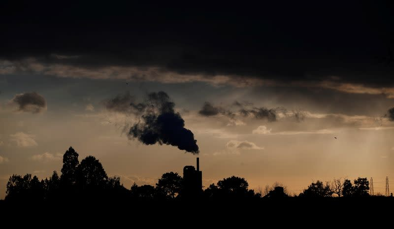 Smoke rises above a factory at sunset in Rugby