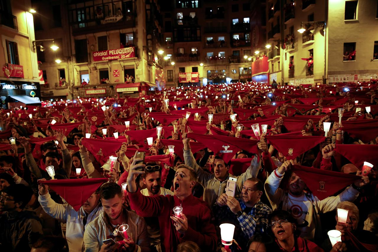 Revellers hold up red scarves and candles during the closing ceremony of the San Fermin festival in Pamplona, northern Spain, early July 15, 2016. REUTERS/Susana Vera