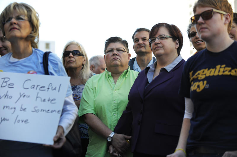 Same sex couple Jayne Rowse , green shirt, and April DeBoer hold hands during the rally outside the federal courthouse in Detroit Wednesday, Oct. 13, 2013. They are involved in a case before the court seeking to overturn Michigan's ban on gay adoption and same-sex marriage. (AP Photo/Detroit News, David Coates) DETROIT FREE PRESS OUT; HUFFINGTON POST OUT