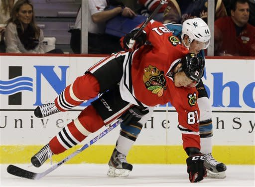 Chicago Blackhawks' Marian Hossa (81) is checked by San Jose Sharks' Marc-Edouard Vlasic (44) during the second period of an NHL hockey game in Chicago, Friday, Feb. 22, 2013. (AP Photo/Nam Y. Huh)