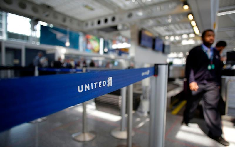An airport worker walking through the United Airlines terminal at O'Hare International Airport in Chicago, Illinois. - AFP