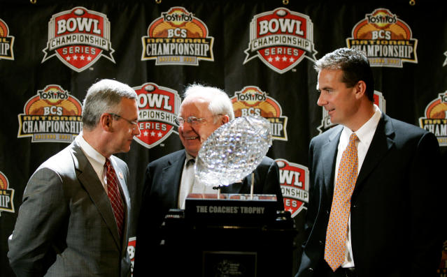 FILE - In this Jan. 7, 2007, file photo, Ohio State head coach Jim Tressel, left, and Florida head coach Urban Meyer, right, are joined by former Ohio State coach Earle Bruce, center, as they stand with the BCS college football championship trophy in Scottsdale, Ariz. Bruce died in Columbus, Ohio at the age of 87, according to a statement released by his daughters through Ohio State on Friday, April 20, 2018. Hed been suffering from Alzheimers disease. (AP Photo/Ted S. Warren, File)