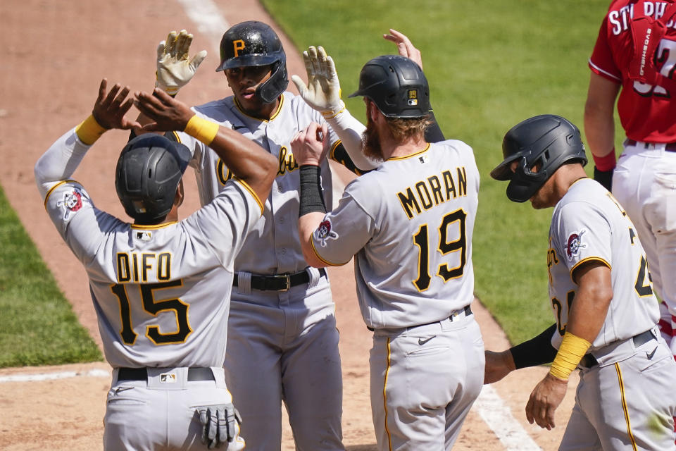 Pittsburgh Pirates' Erik Gonzalez, second from left, celebrates with teammates after hitting a grand slam during the ninth inning of a baseball game against the Cincinnati Reds at Great American Ball Park in Cincinnati, Wednesday, April 7, 2021. (AP Photo/Bryan Woolston)