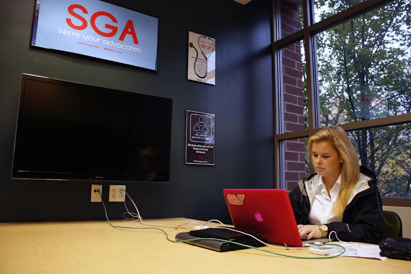 """Caroline Winsett, a senior at DePaul University who is president of the school's Student Government Association, works in the SGA office on Tuesday, Oct. 23, 2012, in Chicago. Winsett, who is 22, is a Republican who considers herself fiscally conservative and socially more liberal _ a political mix that some pollsters say is becoming more common among the youngest voters. It has those pollsters wondering if there is a political """"schism"""" or shift happening when comparing older millennials to younger ones. (AP Photo/Martha Irvine)"""