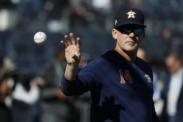 FILE - In this Oct. 15, 2019, file photo, Houston Astros manager AJ Hinch (14) reaches for a ball before Game 3 of baseball's American League Championship Series against the New York Yankees in New York. The Detroit Tigers have hired AJ Hinch to be their new manager, giving him a chance to return to a major league dugout after he was fired by Houston in the wake of the Astros' sign-stealing scandal. (AP Photo/Matt Slocum, File)