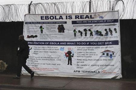 """A man walks by a sign that reads """"Ebola is real"""" in Monrovia"""