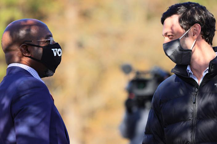 Rev. Raphael Warnock and Jon Ossoff, wearing face masks, face each other