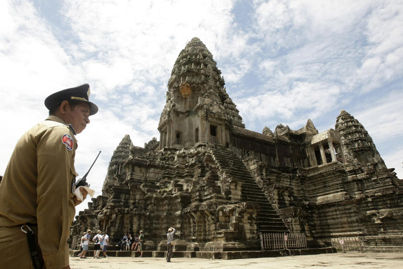 In this photo taken on June 28, 2012, a police officer stands guard at Cambodia's famed Angkor Wat temple complex in Siem Reap province, some 230 kilometers (143 miles) northwest Phnom Penh, Cambodia. Cambodia has joined hands with Australia in an effort to use the Internet to help preserve its fabled Angkor Wat temple complex. The Australian Embassy announced Thursday, July 4, 2013, that a recently-opened website, angkorsunsets.com, will allow tourists to generate recommendations for where in the 160-square-mile (400-square-kilometer) complex one can watch spectacular sunsets. (AP Photo/Heng Sinith)