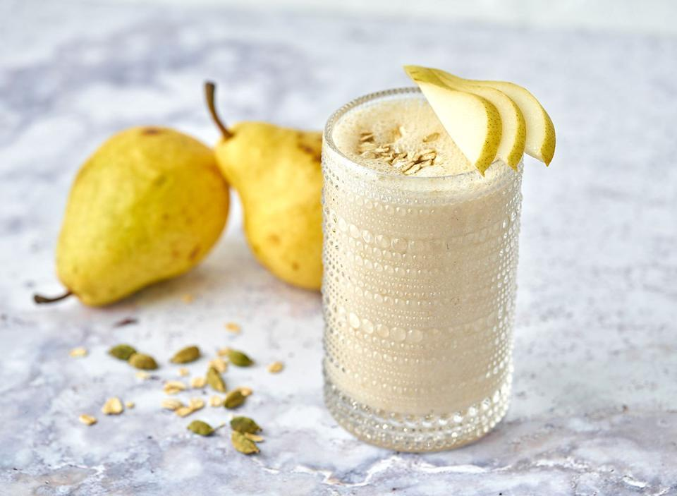 cardamom pear smoothie in glass garnished with pear