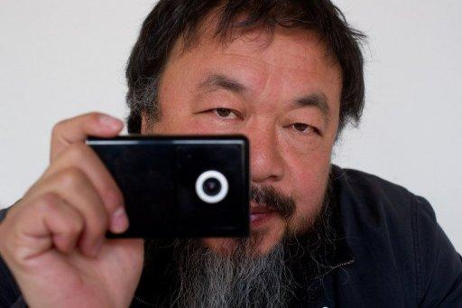 Artist Ai Weiwei holds a webcam that he was reportedly ordered by Chinese police to disconnect