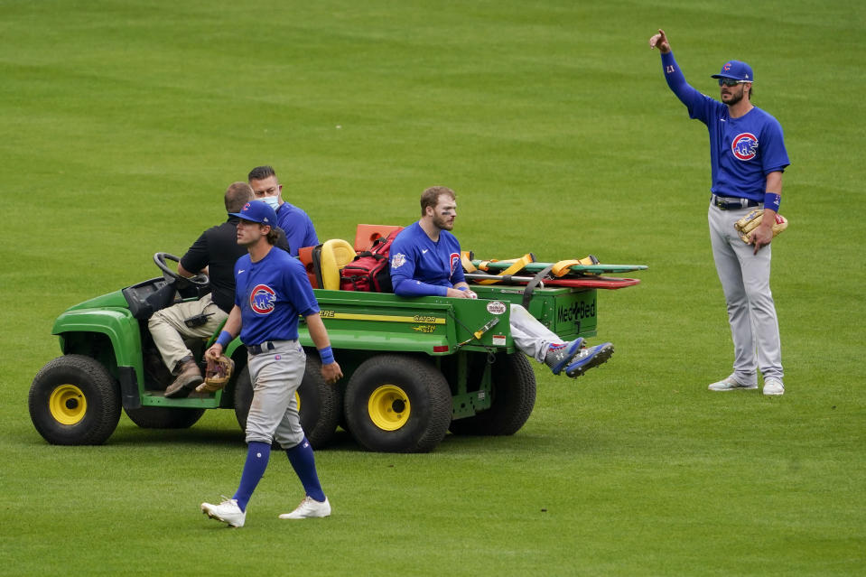 Chicago Cubs center fielder Ian Happ, center, is carted off after a collision with teammate Nico Hoerner, foreground, in the eighth inning during a baseball game against the Cincinnati Reds in Cincinnati on Sunday, May 2, 2021. (AP Photo/Jeff Dean)