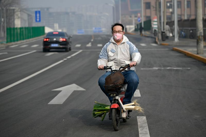 A man wearing a face mask rides his bicycle with a bundle of scallions along a street in Beijing on February 12, 2020. - The number of fatalities from China's deadly COVID-19 coronavirus epidemic jumped to 1,110 nationwide on February 12 after hard-hit Hubei province reported 94 new deaths. (Photo by STR / AFP) (Photo by STR/AFP via Getty Images)