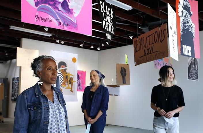 "Brenda Thompson, Peggy Sivert and Tatum Hawkins of SoLA Contemporary stand amid an installation of protest signs. <span class=""copyright"">(Christina House / Los Angeles Times)</span>"