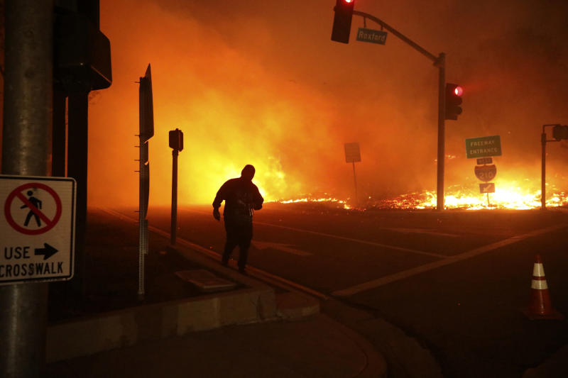 FILE - In this Oct. 11, 2019 file photo, a bystander watches the Saddleridge Fire in Sylmar, Calif. A financial tug-of-war is emerging over the $13.5 billion that Pacific Gas & Electric, the nation's largest utility, has agreed to pay to victims of recent California wildfires, as government agencies jockey for more than half the money to cover the costs of their response to the catastrophes. (AP Photo/David Swanson, File)