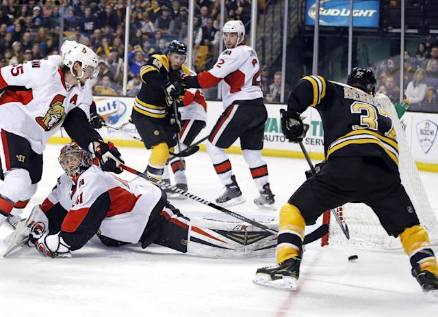 Boston Bruins center Patrice Bergeron (37) maneuvers the puck for a goal as Ottawa Senators goalie Craig Anderson (41) lies on the ice with Senators defenseman Erik Karlsson (65) trying to defend during the second period of an NHL hockey game in Boston, Saturday, Feb. 8, 2014. Senators defenseman Jared Cowen (2) covers Bruins right wing Reilly Smith (18). (AP Photo/Elise Amendola)
