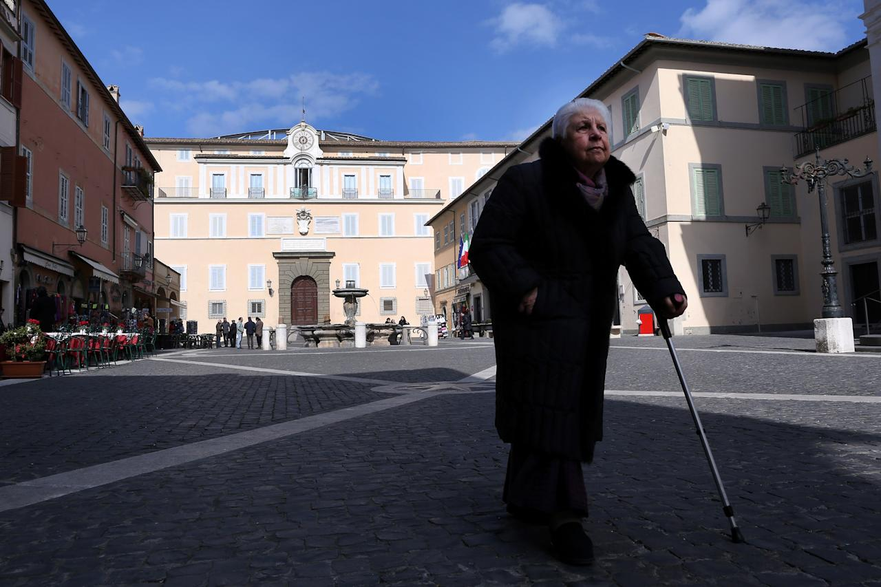 ROME, ITALY - FEBRUARY 20:  A woman waks in the Apostolic Palace in the main square of Castelgandolfo, where Benedict XVI will make his last public appearance as Pope, on February 20, 2013 in Rome, Italy. The Apostolic Palace and The Ponifical Villas of Castelgandolfo, 10 miles south Rome, are the summer residence of Popes and will host  Pope Benedict XVI during the next conclave.  (Photo by Franco Origlia/Getty Images)