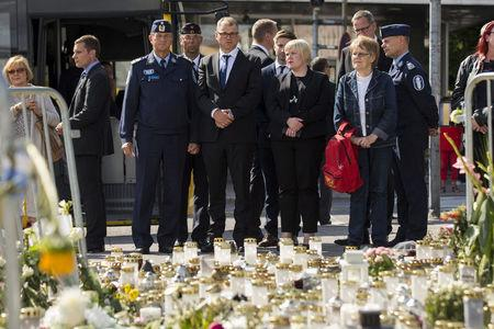 The Chief of Turku Police Tapio Huttunen, Finland's Prime Minister Juha Sipila and Finnish parliament member Annika Saarikko stand next to the memorial flowers at the Turku Market Square, in Turku