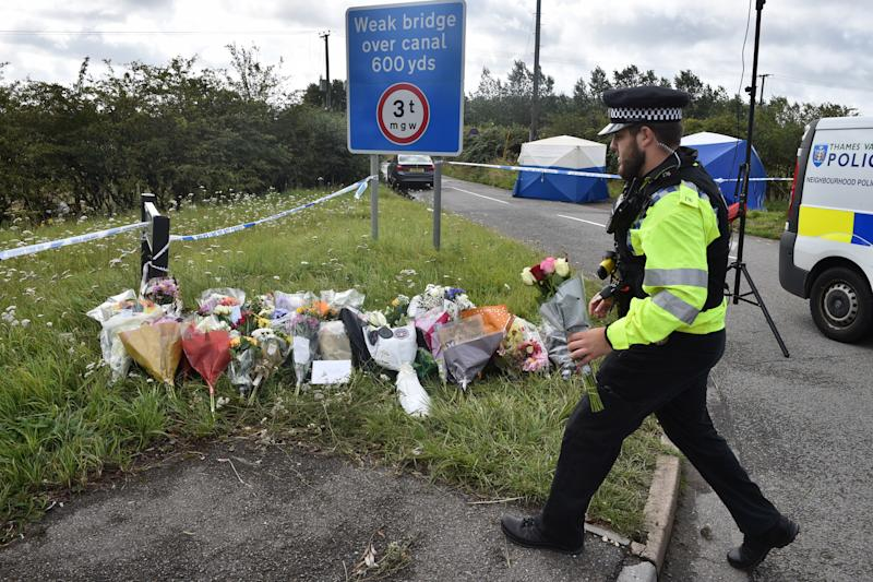 A police officer lays a floral tribute at the scene where Thames Valley Police officer Pc Andrew Harper died in Sulhamstead, Berkshire (Picture: PA)