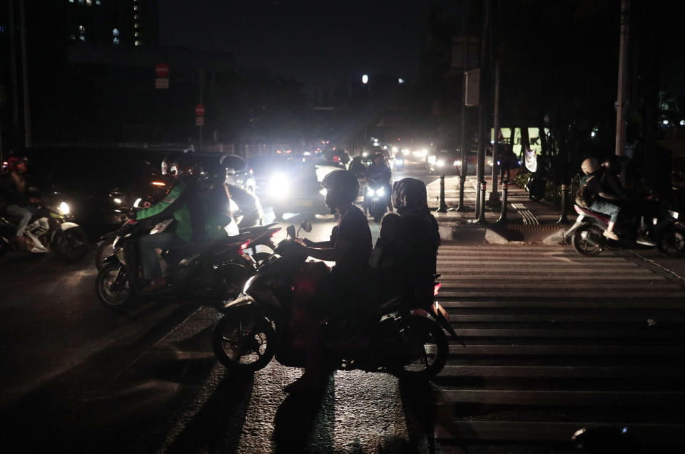 Motorists navigate through traffic during a power outage in Jakarta, Indonesia, Sunday, Aug. 4, 2019. Indonesia's sprawling capital and other parts of Java island have been hit by a massive power outage affecting millions of people. (AP Photo/Dita Alangkara)